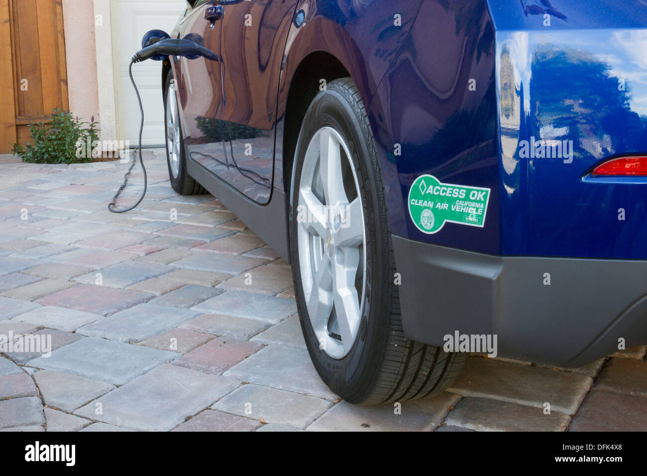 Plug in electric car with carpool sticker parked in driveway with plug in electric car with carpool sticker parked in driveway with connector plugged in and charging at home biocorpaavc Images