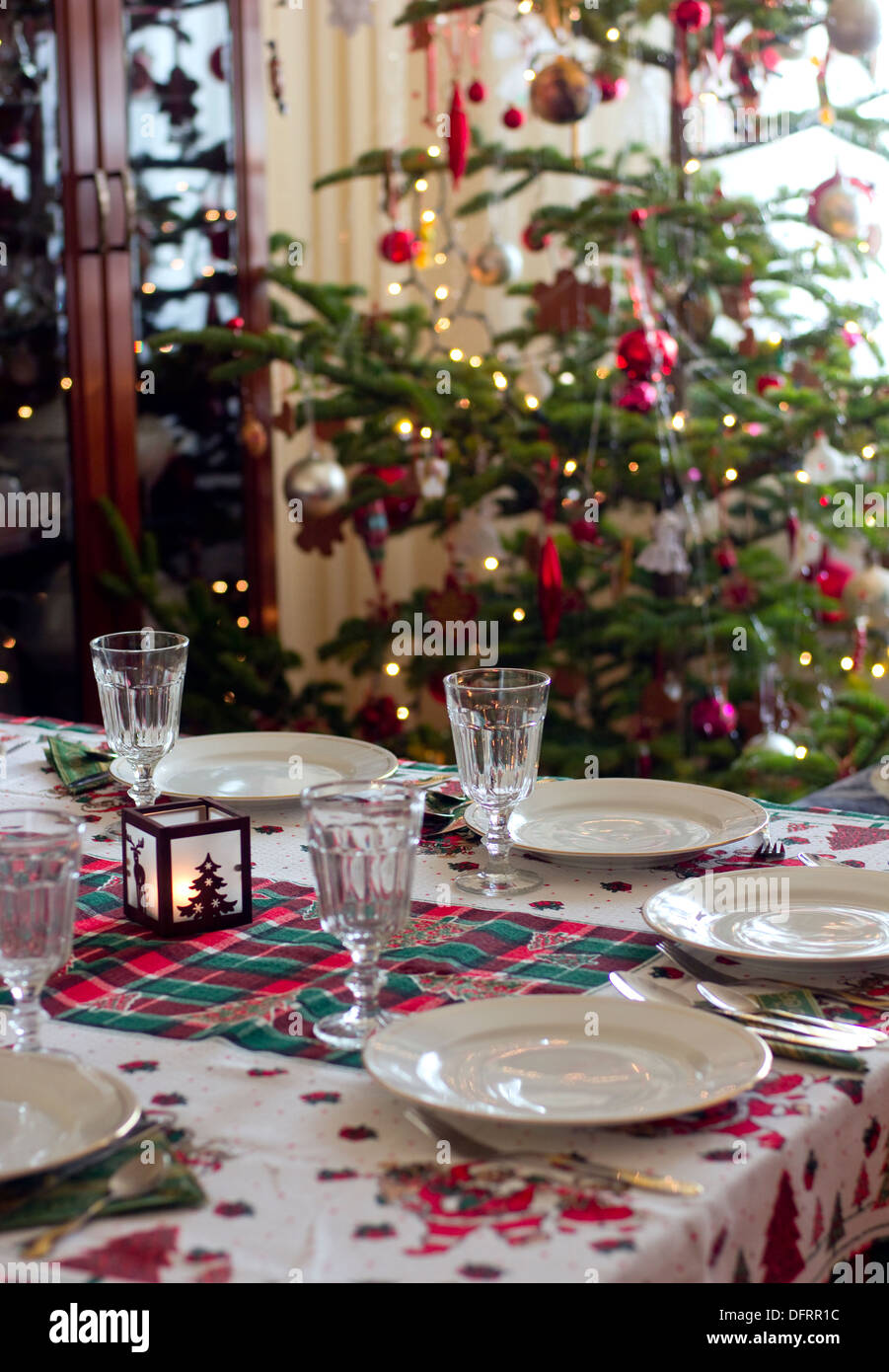 table prepared for christmas dinner against christmas tree in the ...