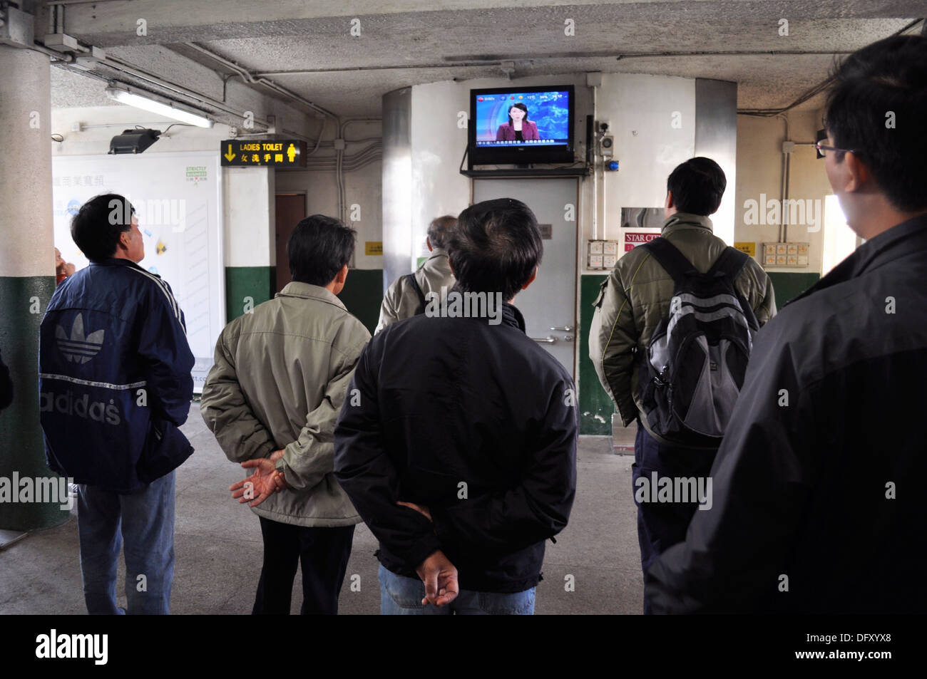 hong kong men watching tv while waiting for the star ferry in hong kong men watching tv while waiting for the star ferry in victoria harbour