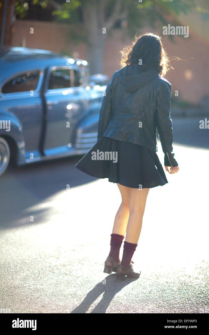Girl Walks Into Door : Teenage girl walking into sunlit street with vintage car
