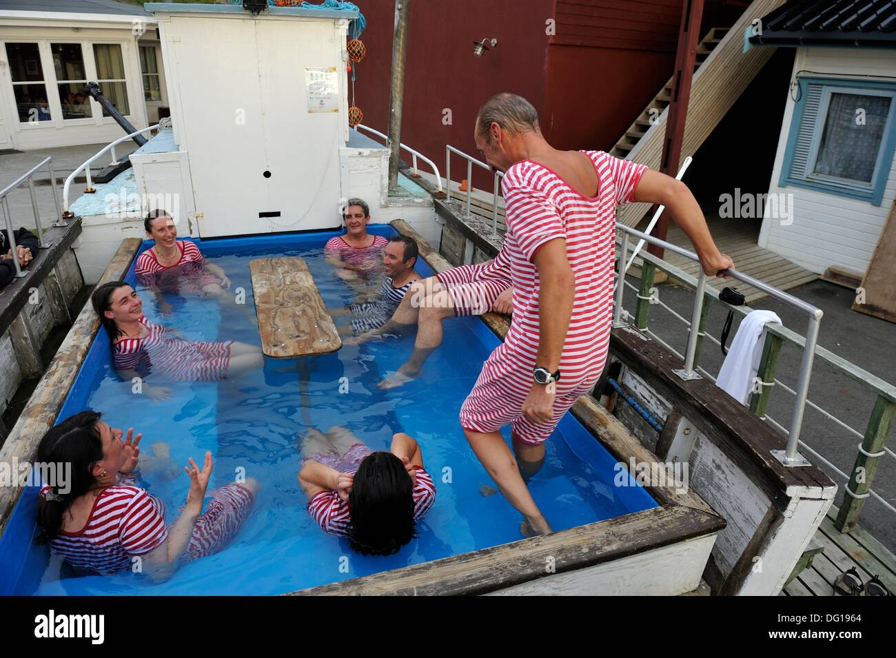 people bathing in an outdoor hot tub settled in a boat, dressed ...