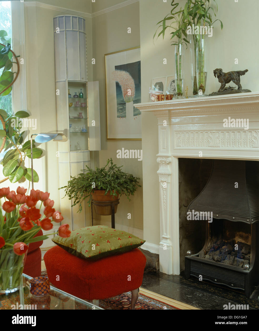 Cream silk cushion on red upholstered stool beside fireplace in ...