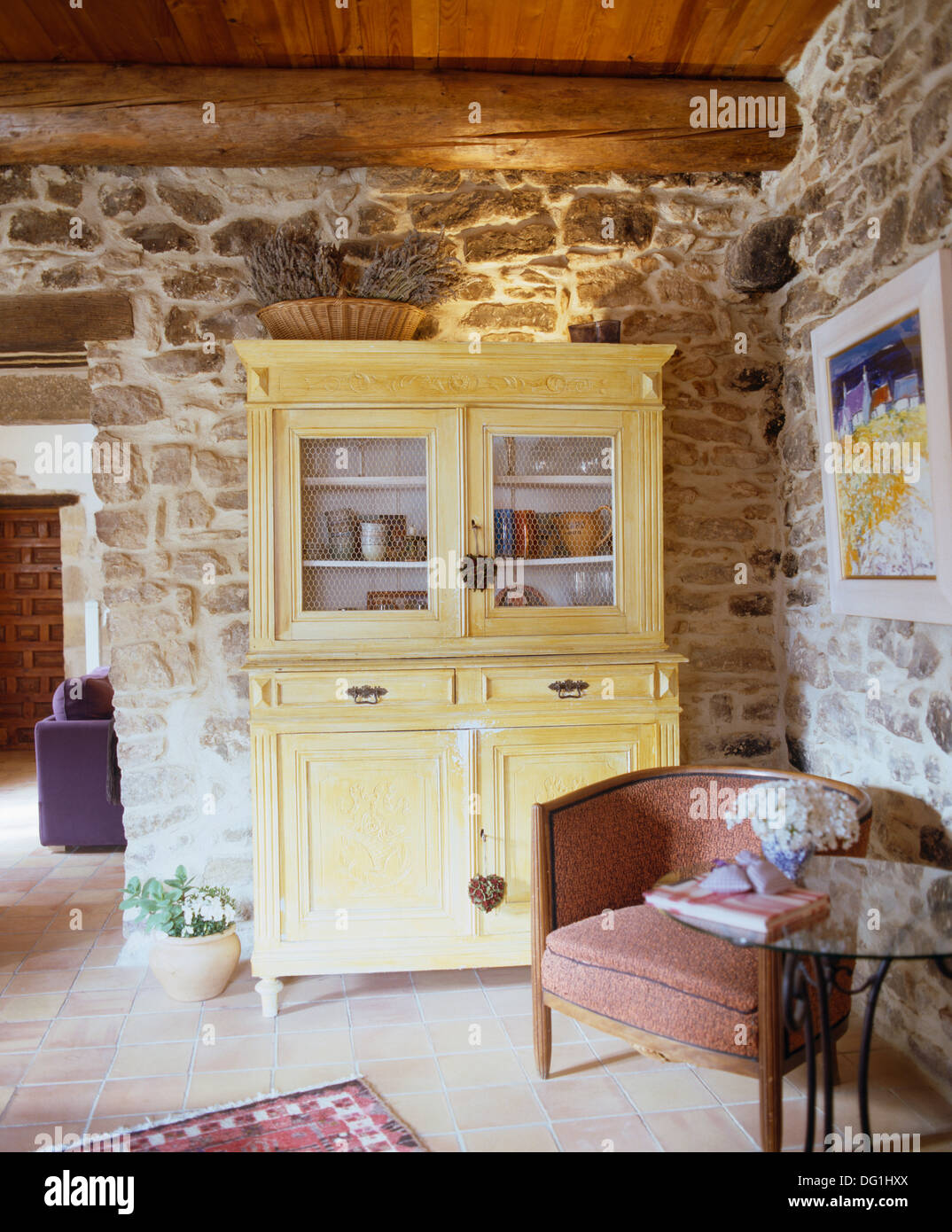 Stripped Wood Dresser And Small Tub Chair In French Country Dining Room With Exposed Stone Walls