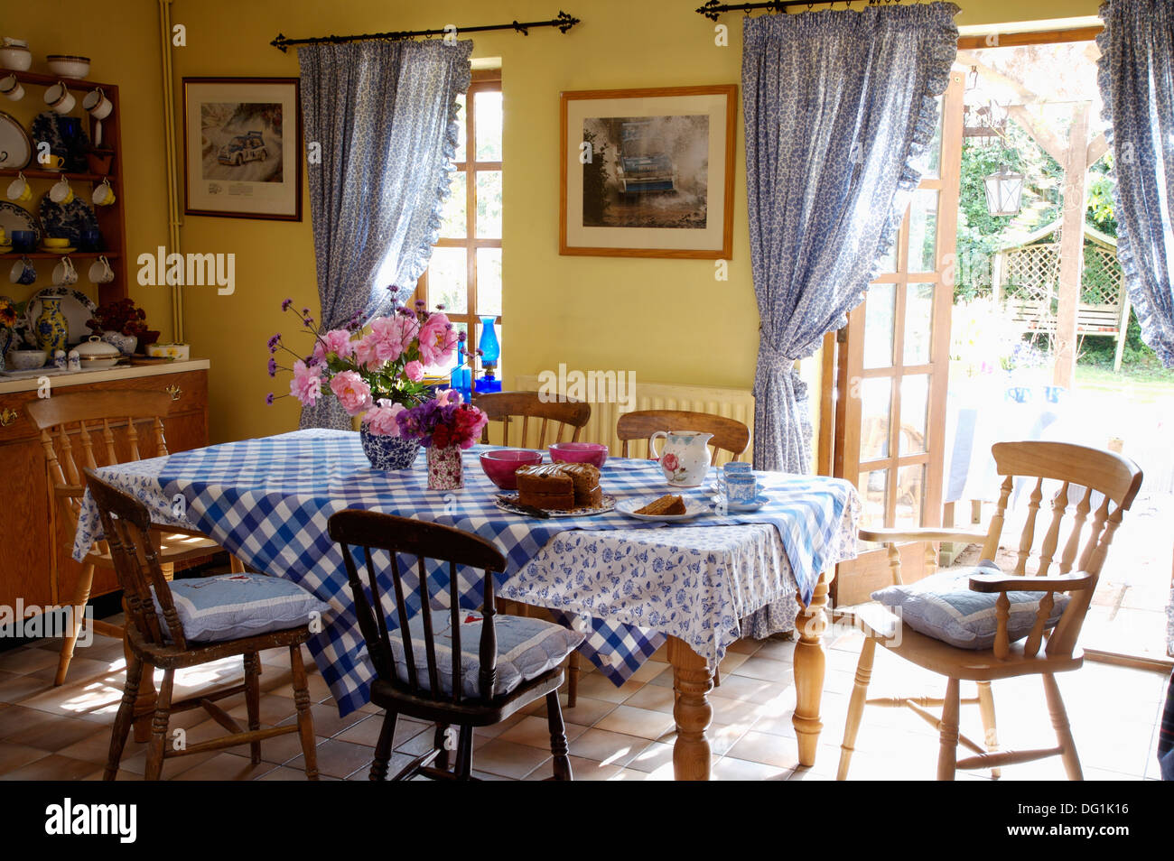 Blue Checked Cloth On Table With Stick Back Chairs In Yellow Dining Room  With Blue Curtains At French Windows To The Garden