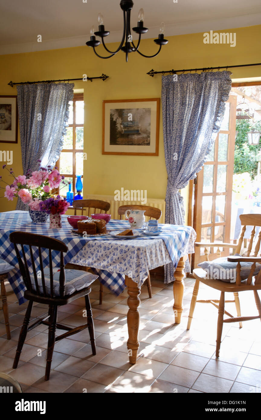 Blue Checked Cloth On Table With Stick Back Chairs In Yellow Dining Room Tiled Floor And Curtains At French Windows