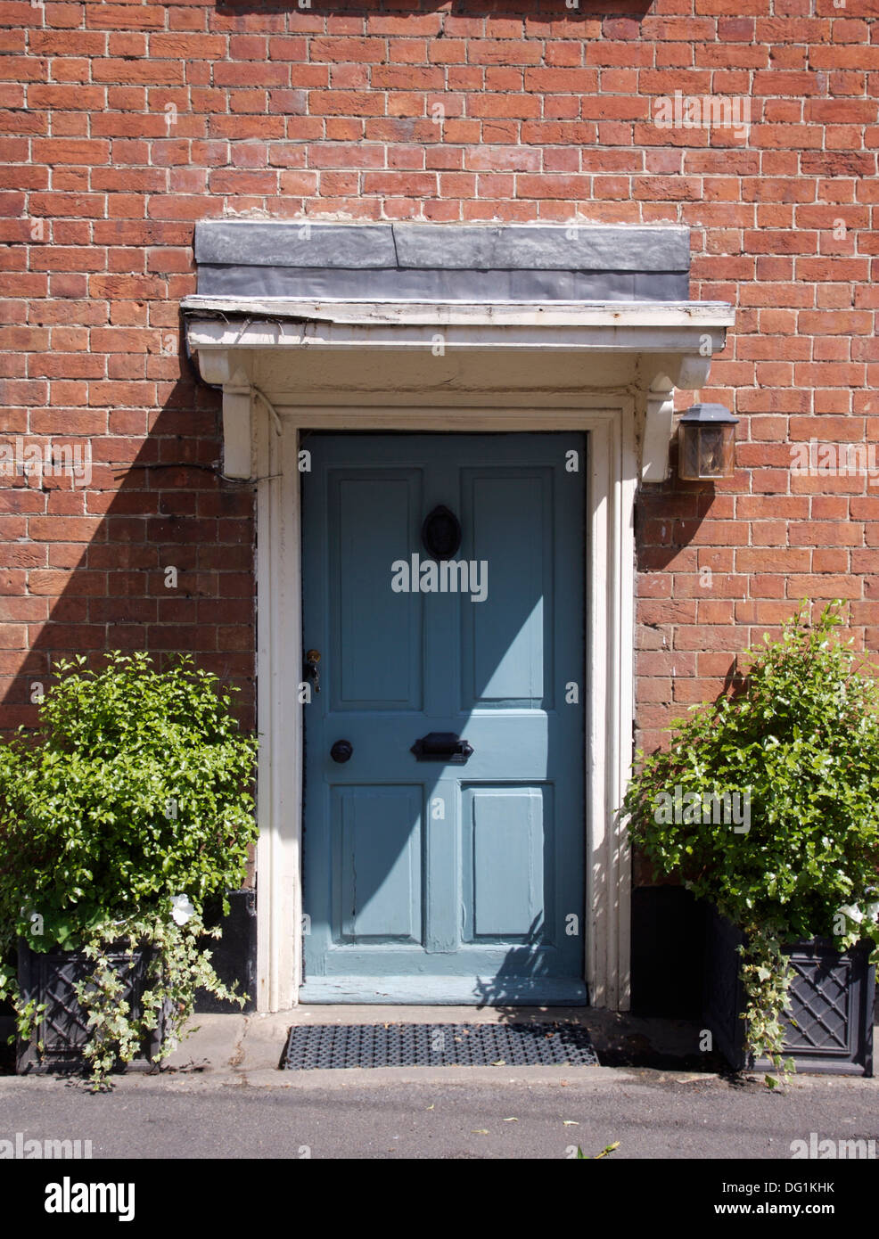 Green shrubs in pots on either side of blue front door in for Blue green front door