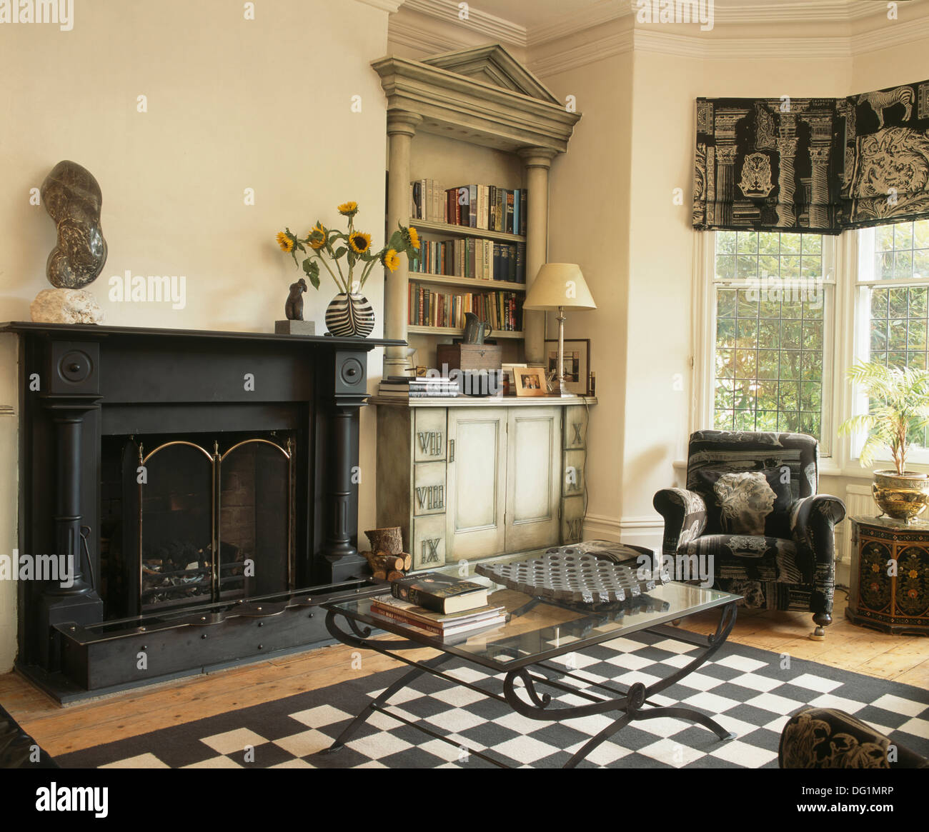 Glass topped coffee table and black+white checkerboard rug in front of  fireplace in living