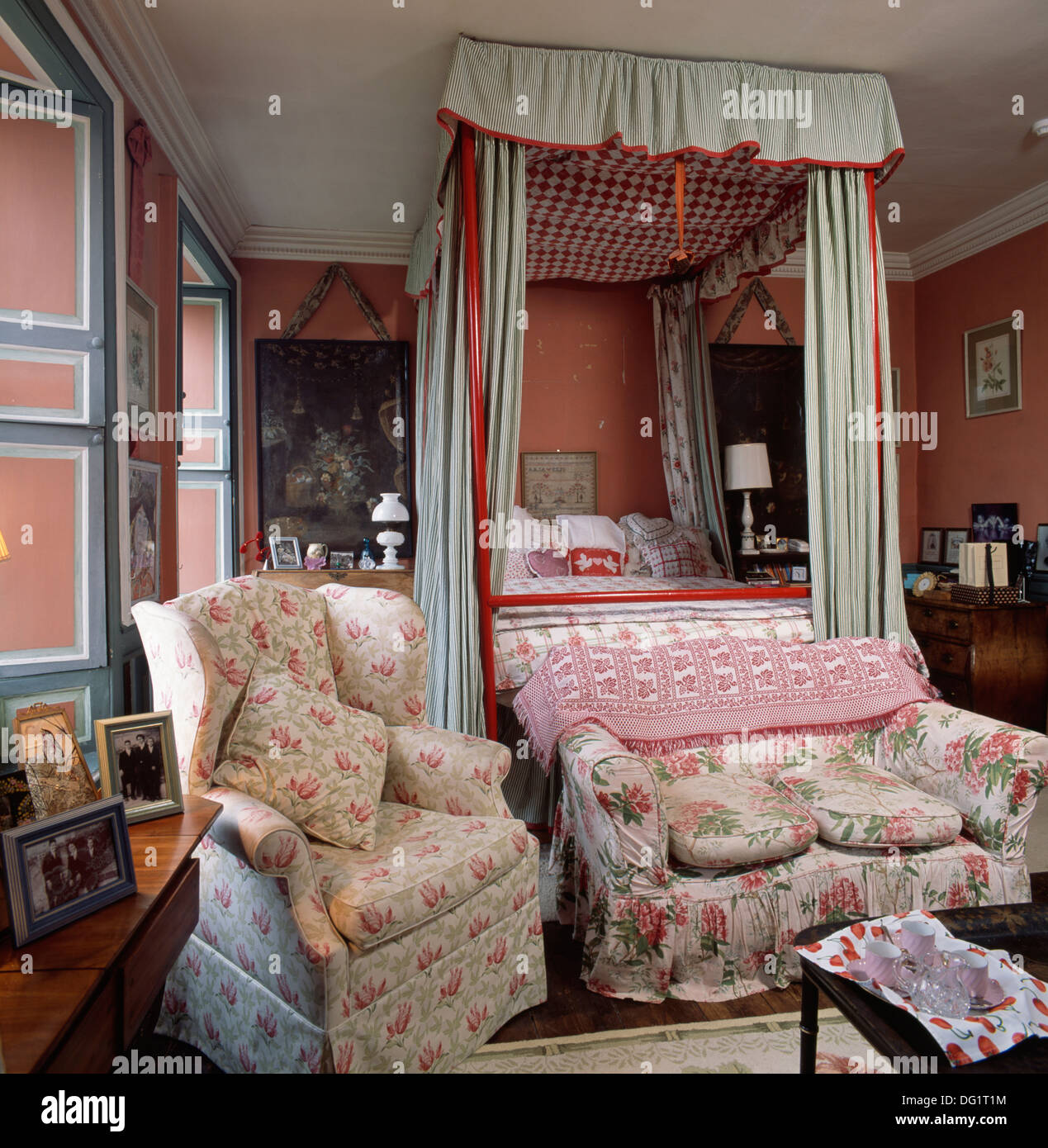 Floral patterned sofa and armchair in traditional bedroom with red ...