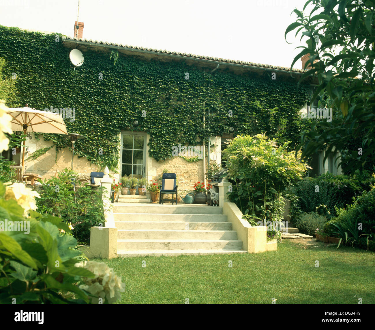 stone steps up to patio in front of ivy clad traditional french