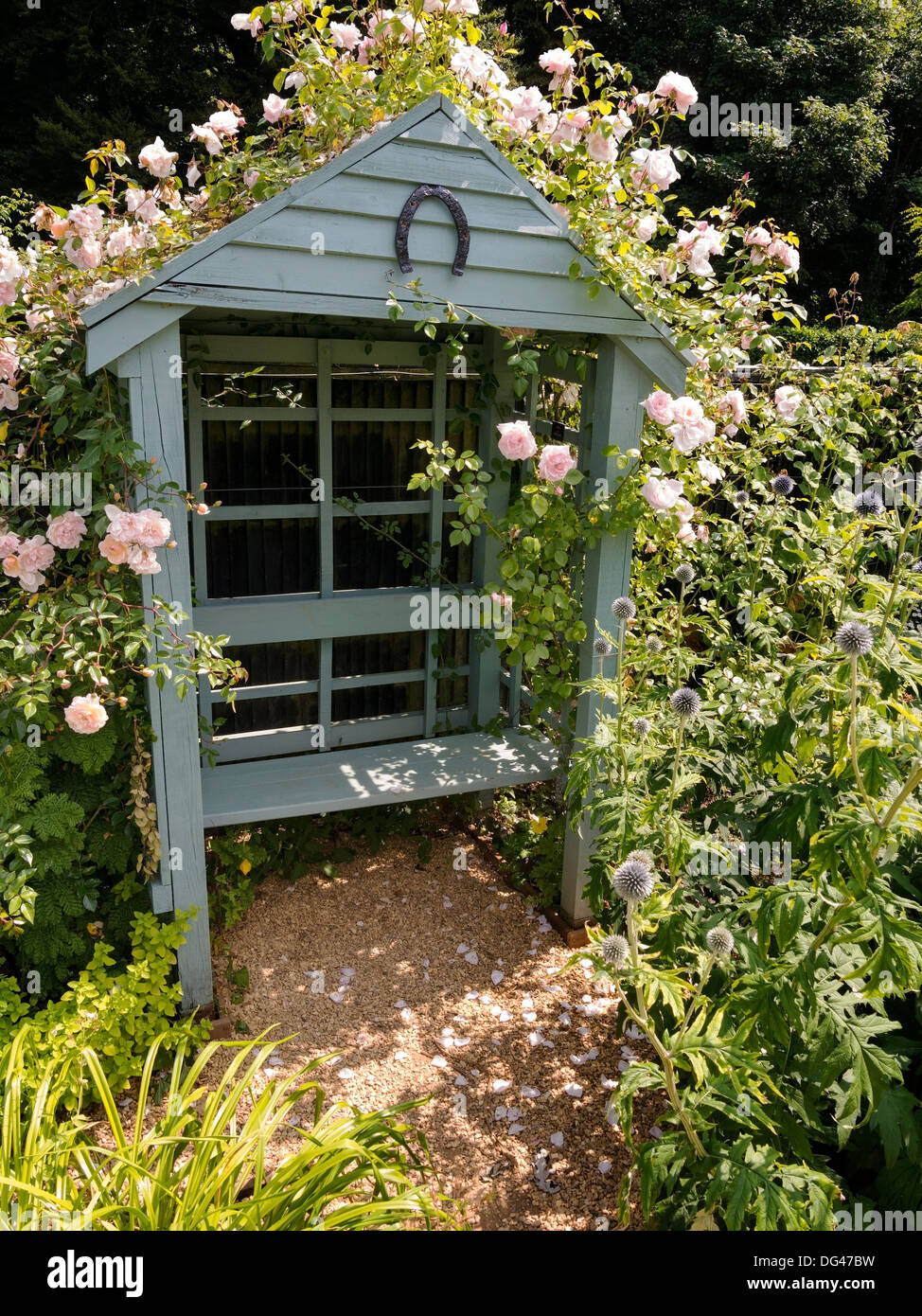 Ornate wooden garden arbor with bench seat and climbing roses in