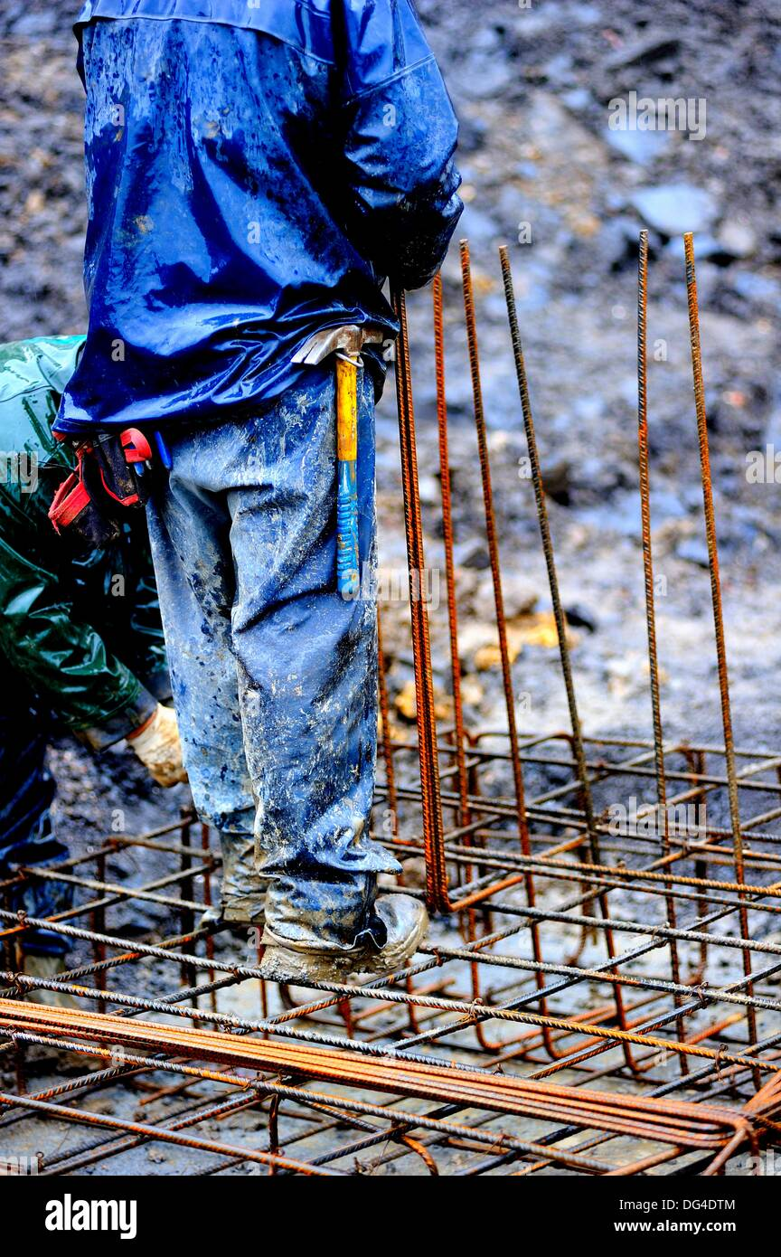 high contrast image of a worker assembling a rebar frame for mounting a concrete structure