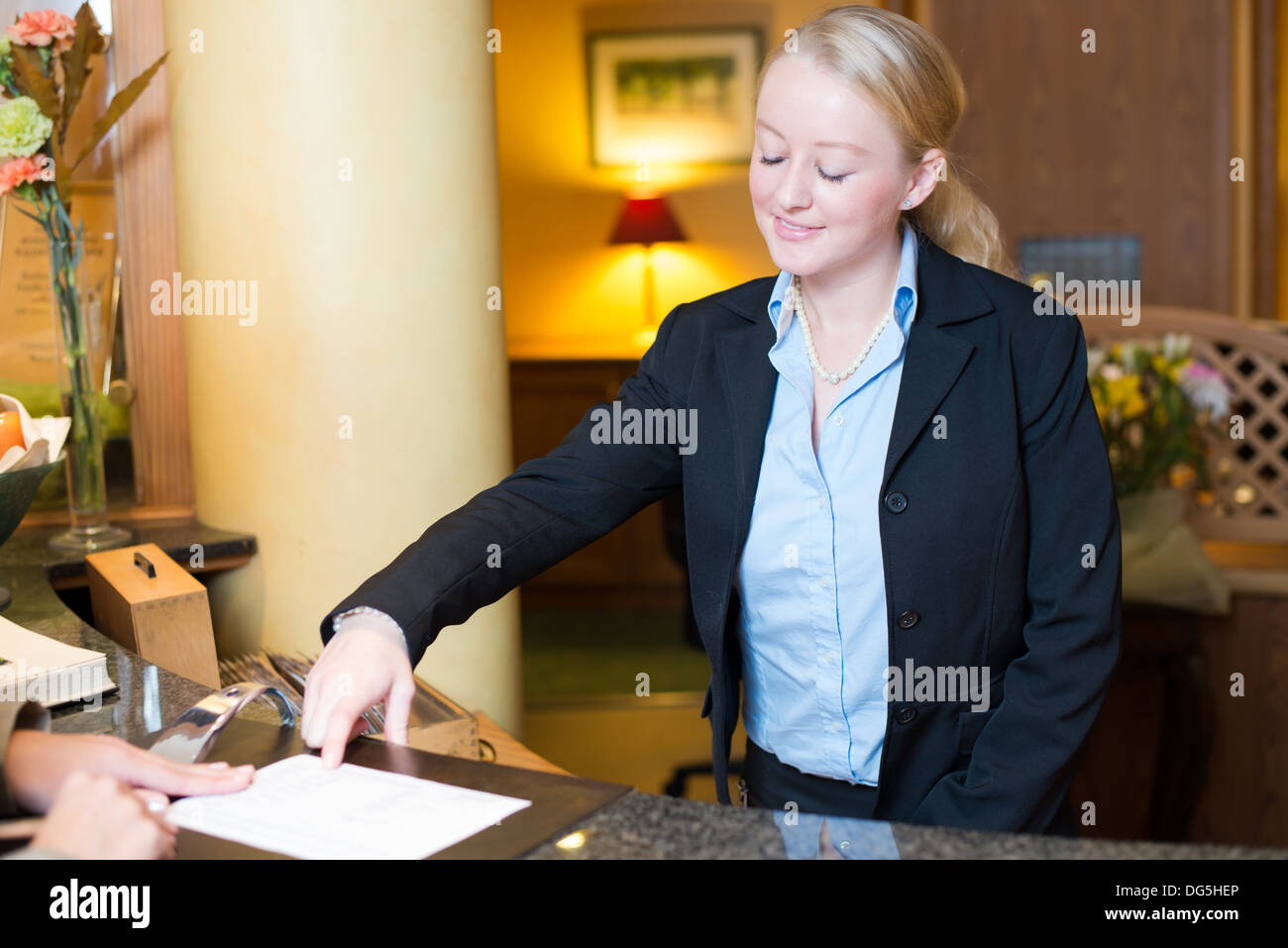 young female receptionist at hotel desk Stock Photo ...