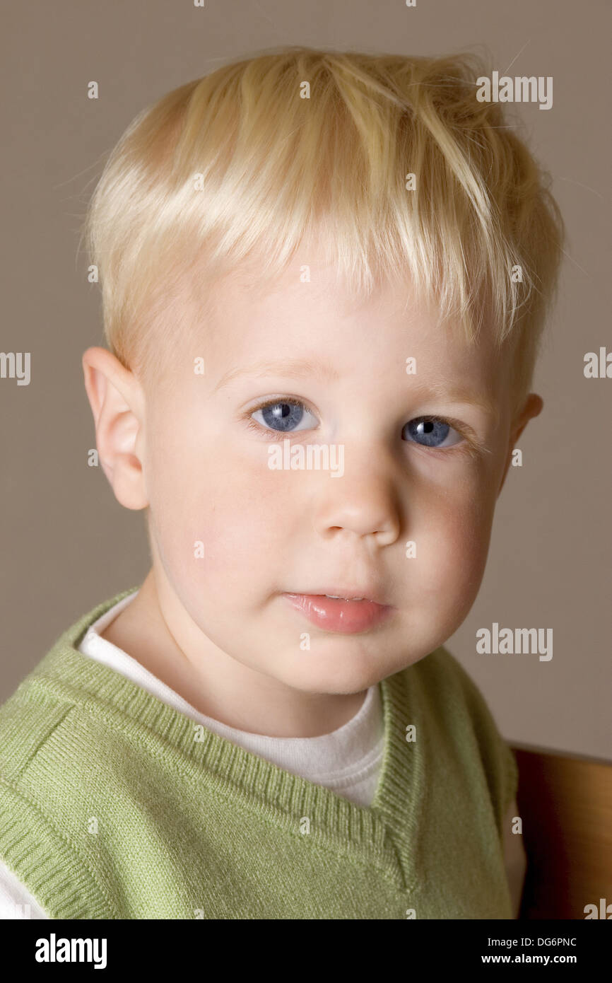 A Blonde Hair Blue Eyed Two Year Old Boy Looks Straight At The
