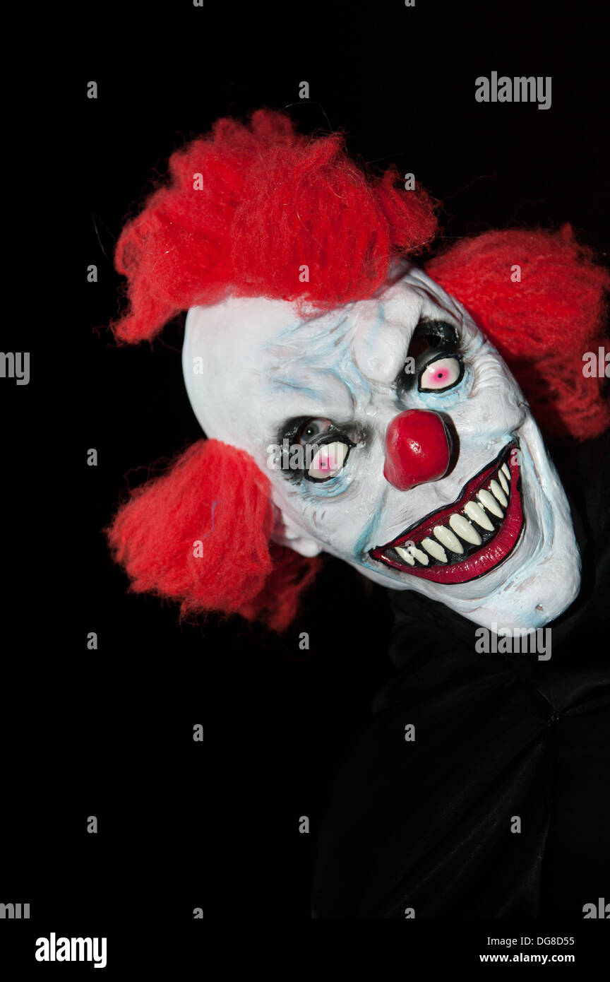 a scary halloween clown mask against a black background