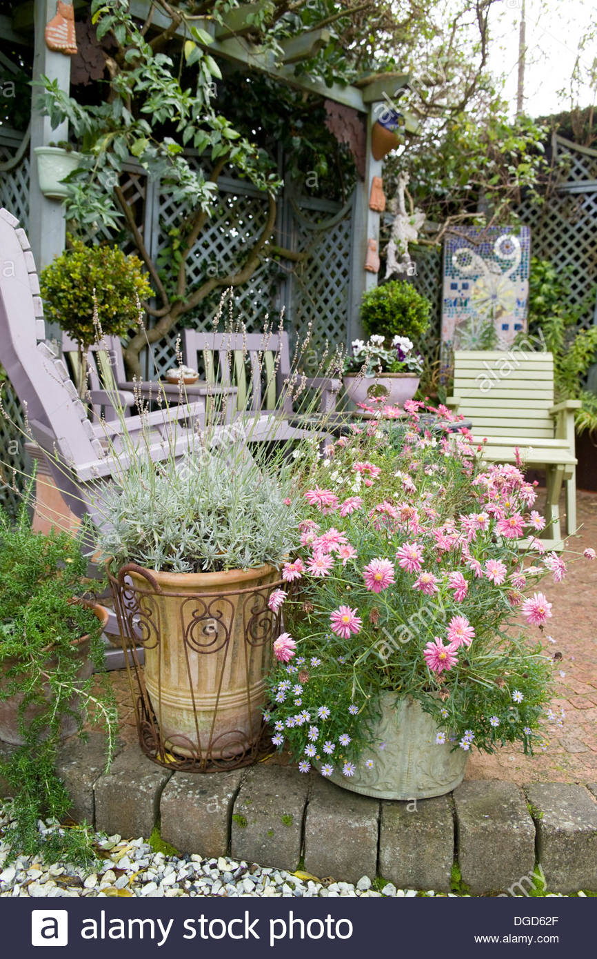 Attractive Patio In Garden With Late Summer Flowers In Containers, Painted Furniture  And Trellis With Climbing Plants