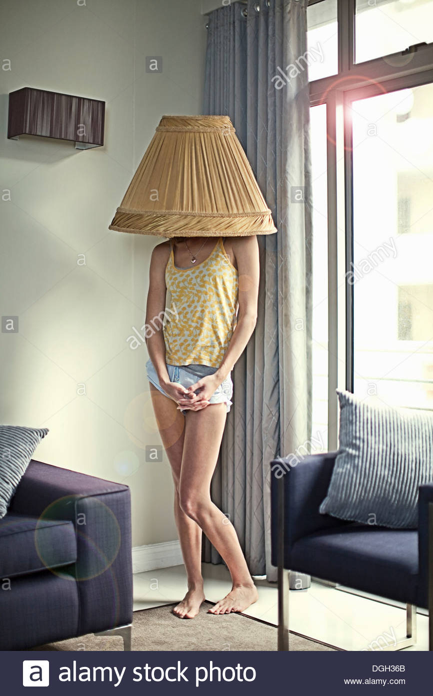 Lamp Shade On Head : Young woman wearing lampshade on head stock photo royalty