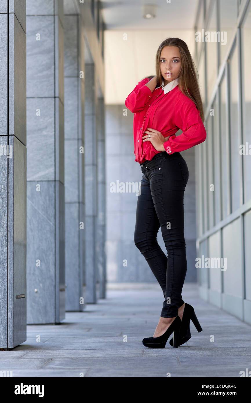 Young woman wearing a red top, black jeans and high heels Stock ...