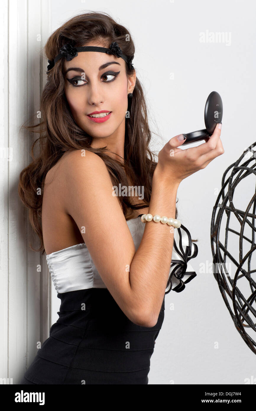 Young woman holding make up powder with a mirror in her hand Stock