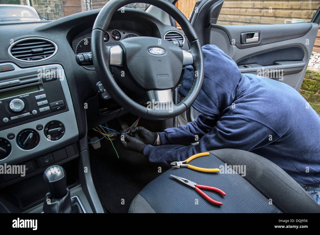 A man wearing a hoody hot wiring a car. : hot wiring - yogabreezes.com