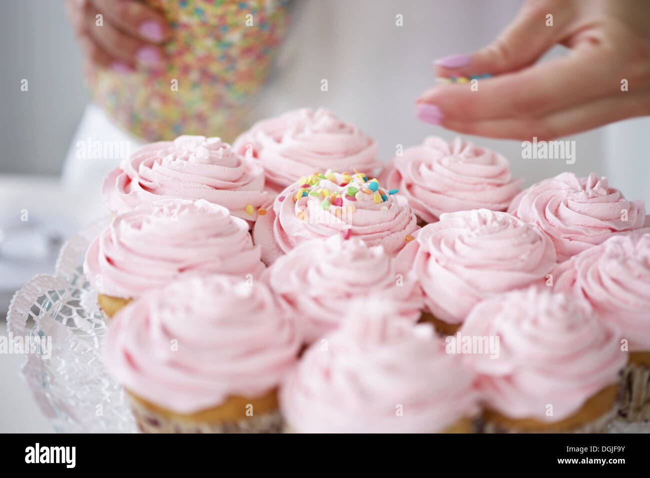 stock photo woman decorating cupcakes with sugar sprinkles