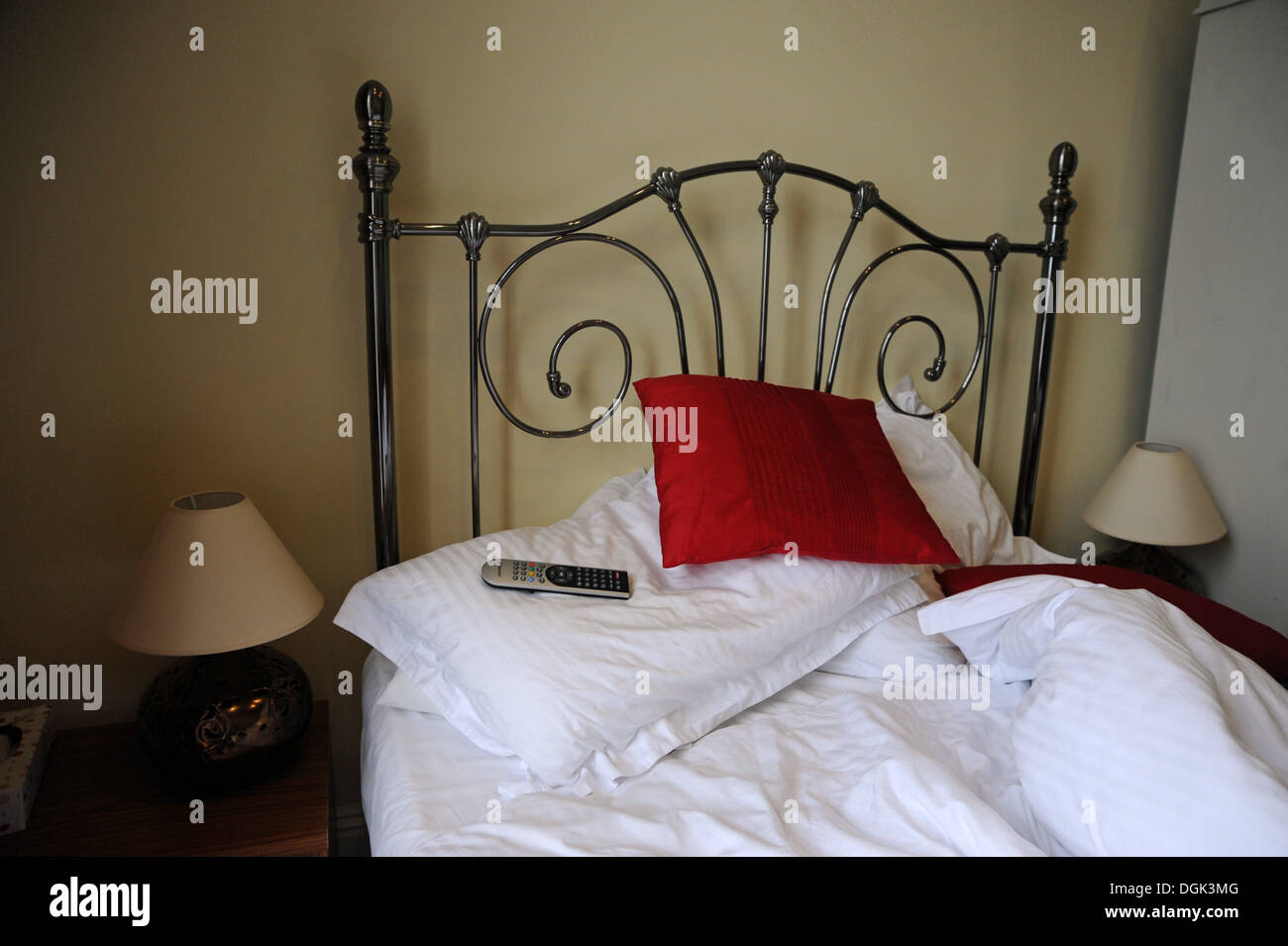 unmade bed with tv remote control on pillows stock photo, royalty