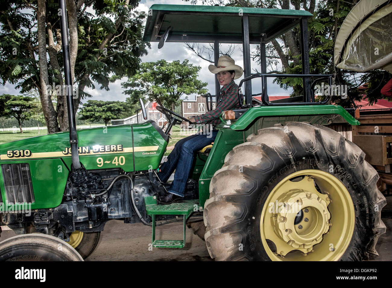 Female Thai farm worker driving a John Deere tractor ...