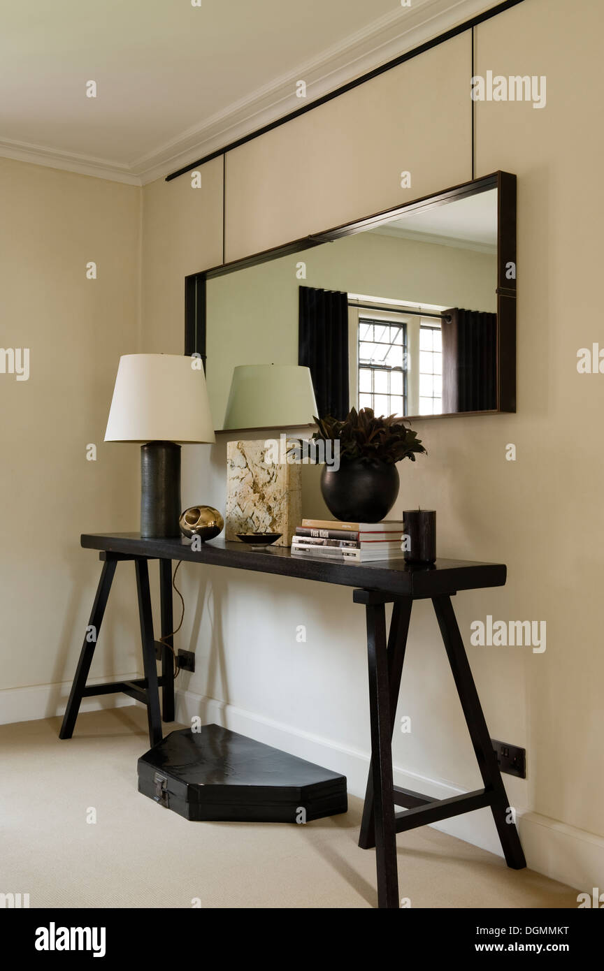 Rectangular mirror above console table in bedroom of 1030s Tudor