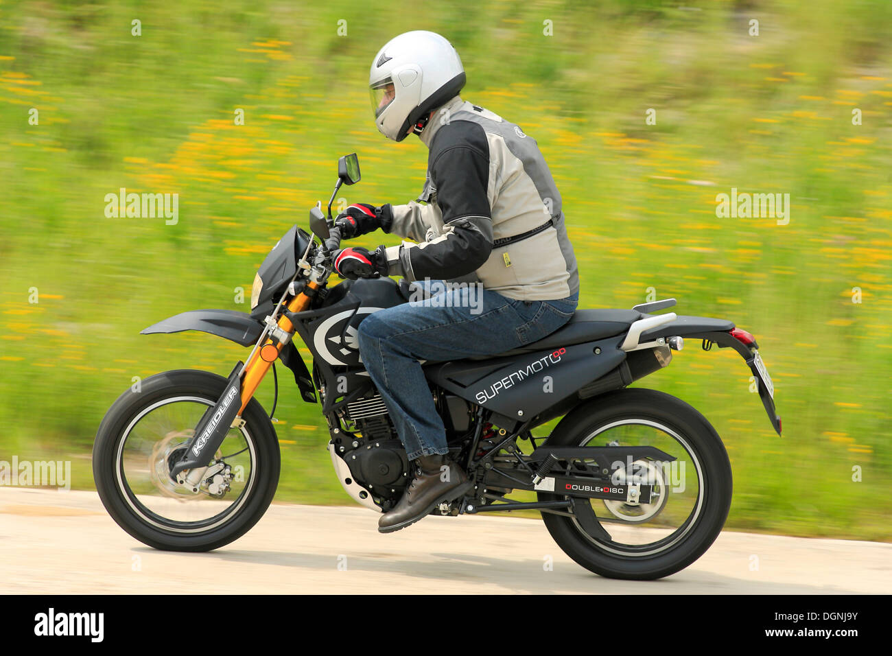 motorcyclist riding a kreidler supermoto 125 dd scooter. Black Bedroom Furniture Sets. Home Design Ideas