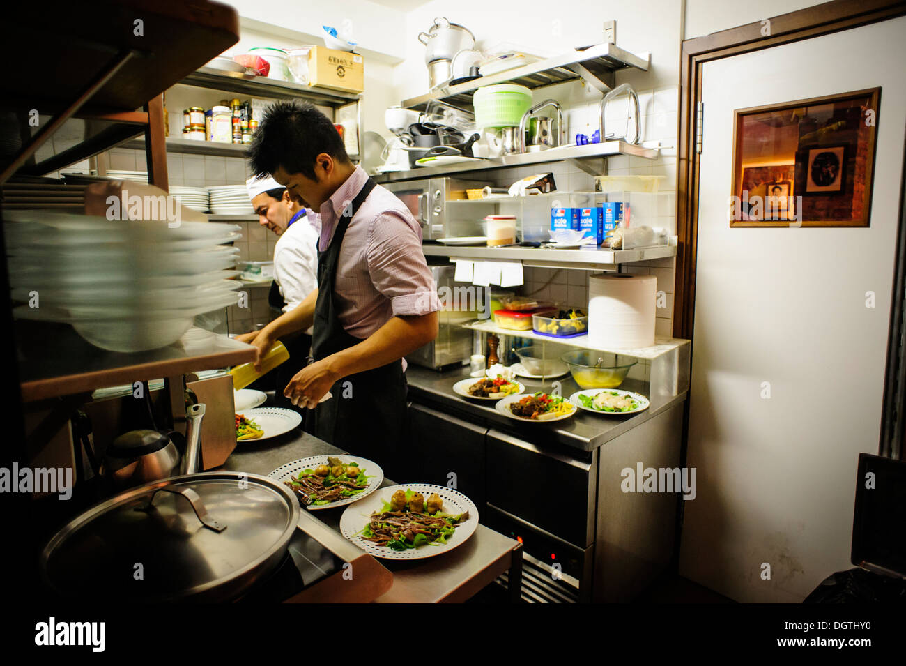 People working in a small professional kitchen la for Kitchen 8 restaurant