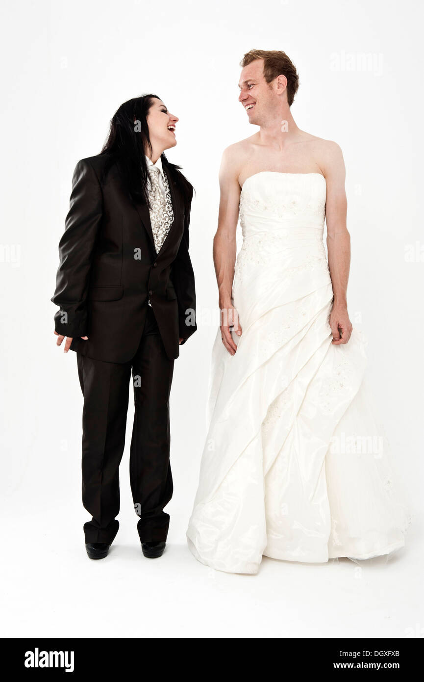 Bride wearing a suit and a groom wearing a wedding dress smiling ...