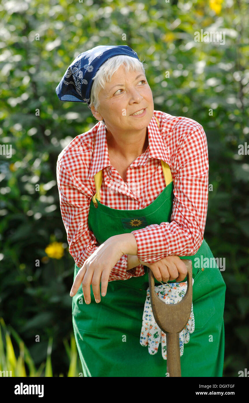 Amazing Elderly Woman, Gray Haired, 55 65, Wearing Gardening Clothes And Leaning  Against A Spade In A Garden