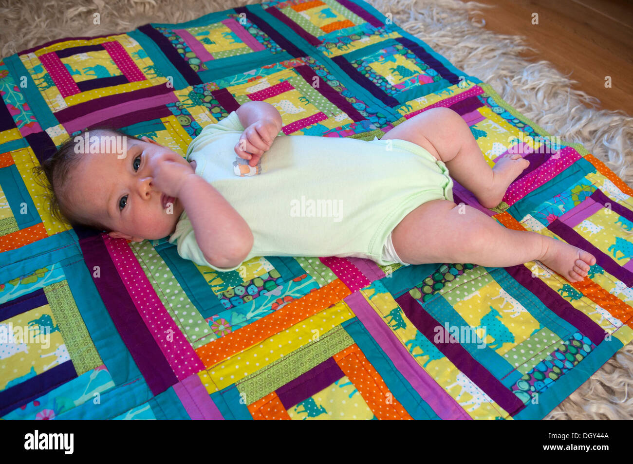 Little baby girl lying down on a colourful patchwork quilt looking ... : colourful patchwork quilt - Adamdwight.com