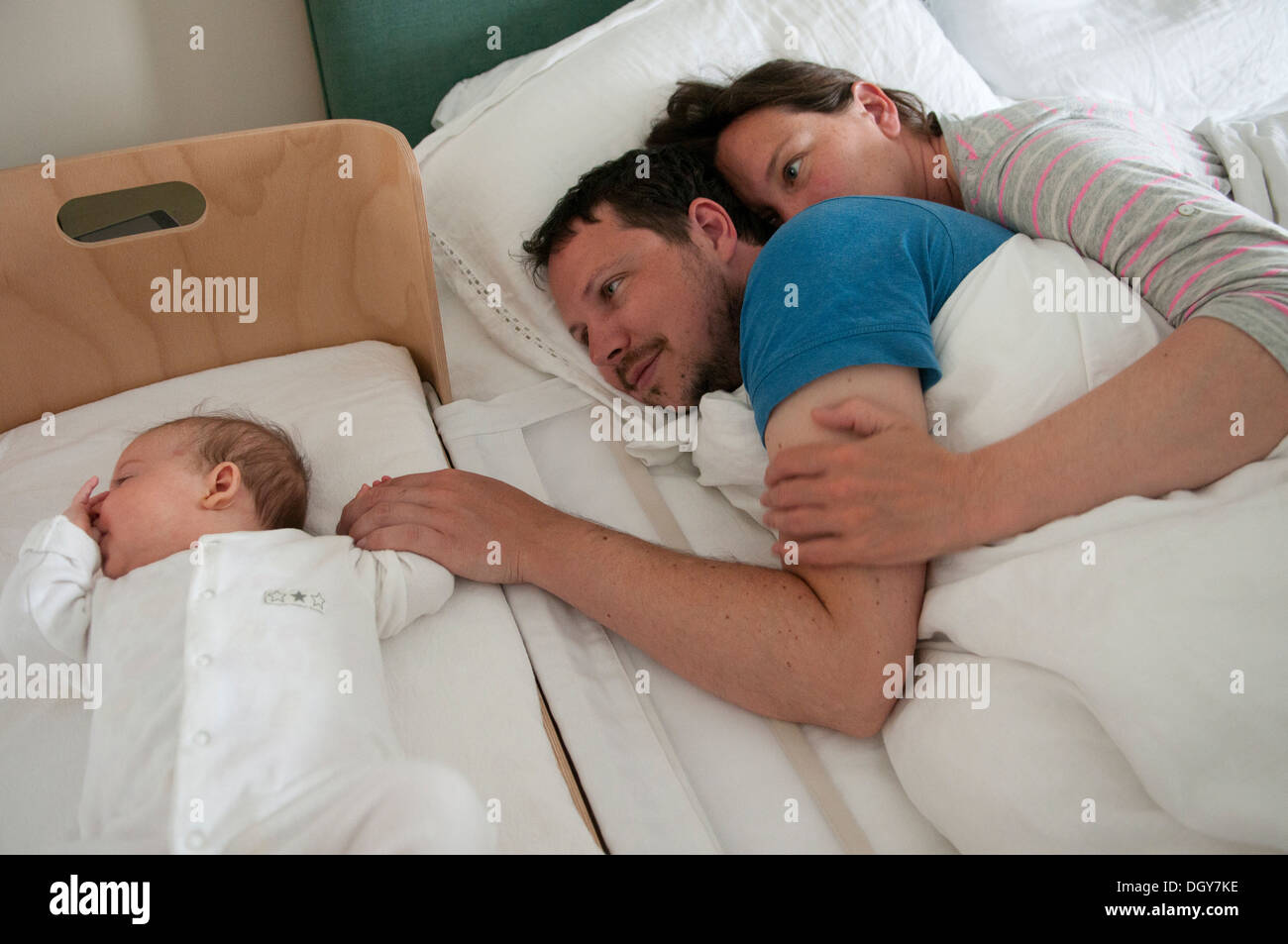 Baby bed with parents - New Parents In Bed Cuddling Both Awake With Dad Comforting His Little Baby Girl And