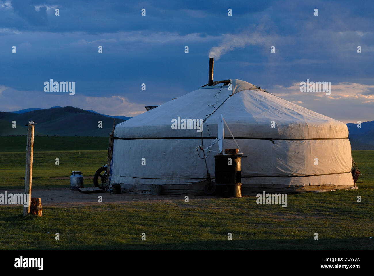 Mongolian ger or yurt a round tent in the evening light with a smoking furnace in grassland at Orkhon Waterfall & Mongolian ger or yurt a round tent in the evening light with a ...