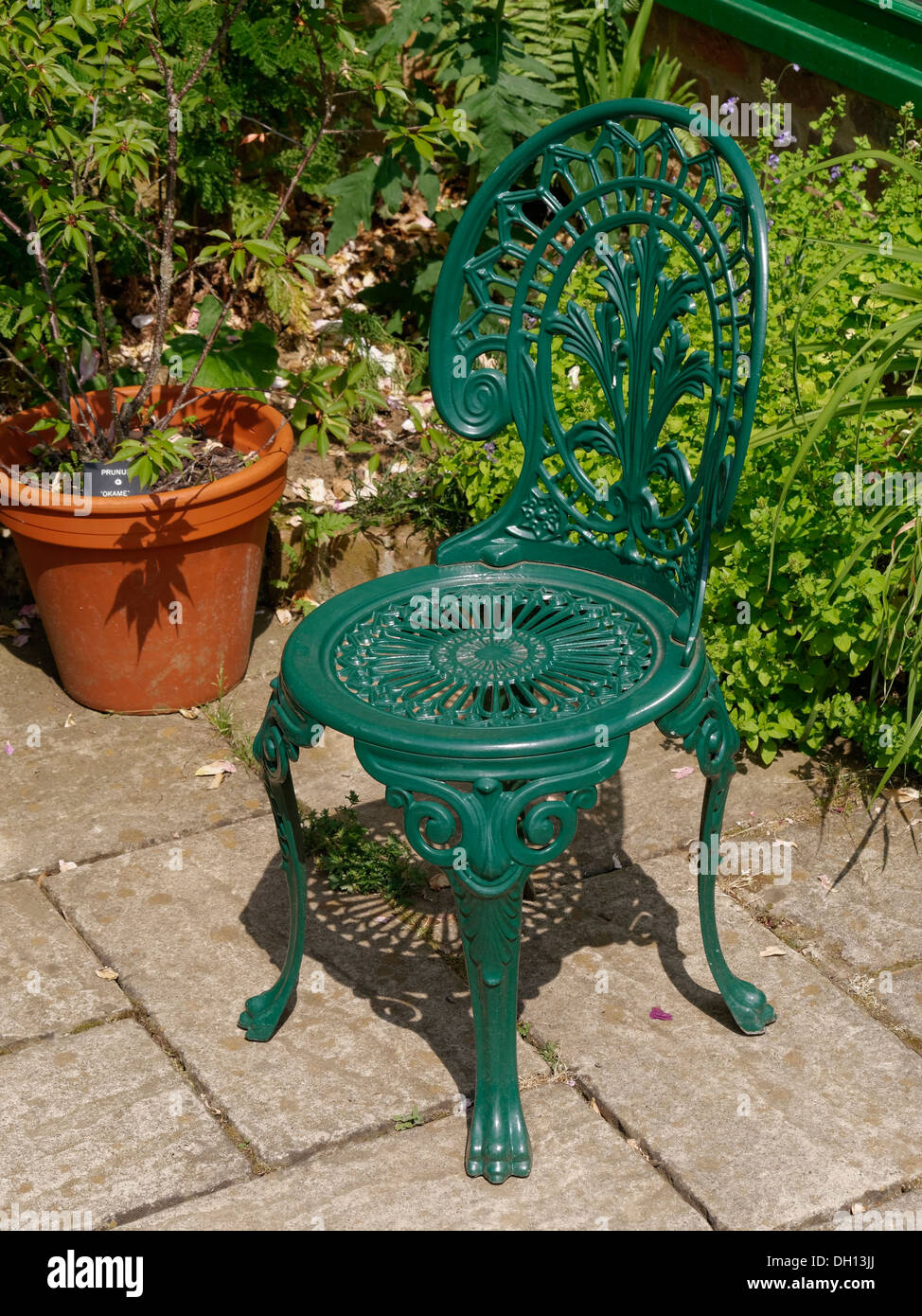 Green painted ornate cast metal garden chair on slabbed patio  Barnsdale  Gardens  Oakham  Rutland  England  UK. Green painted ornate cast metal garden chair on slabbed patio