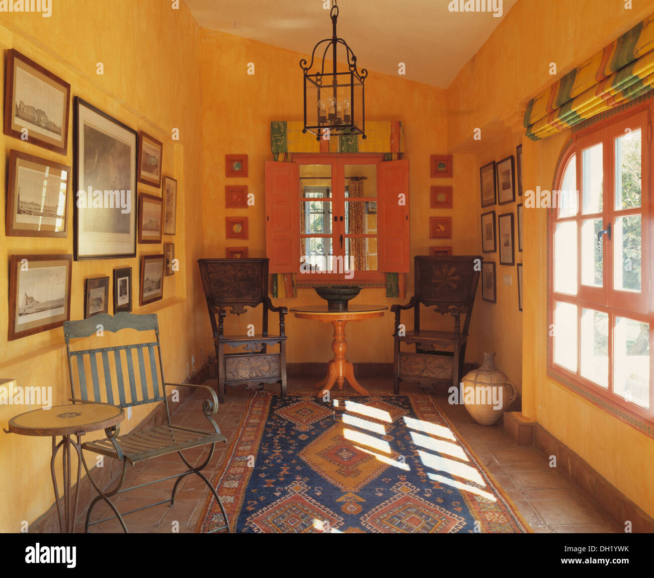 Patterned Rug In Yellow Spanish Dining Room With Antique Wooden Chairs At Painted Table Front Of Window Orange Shutters