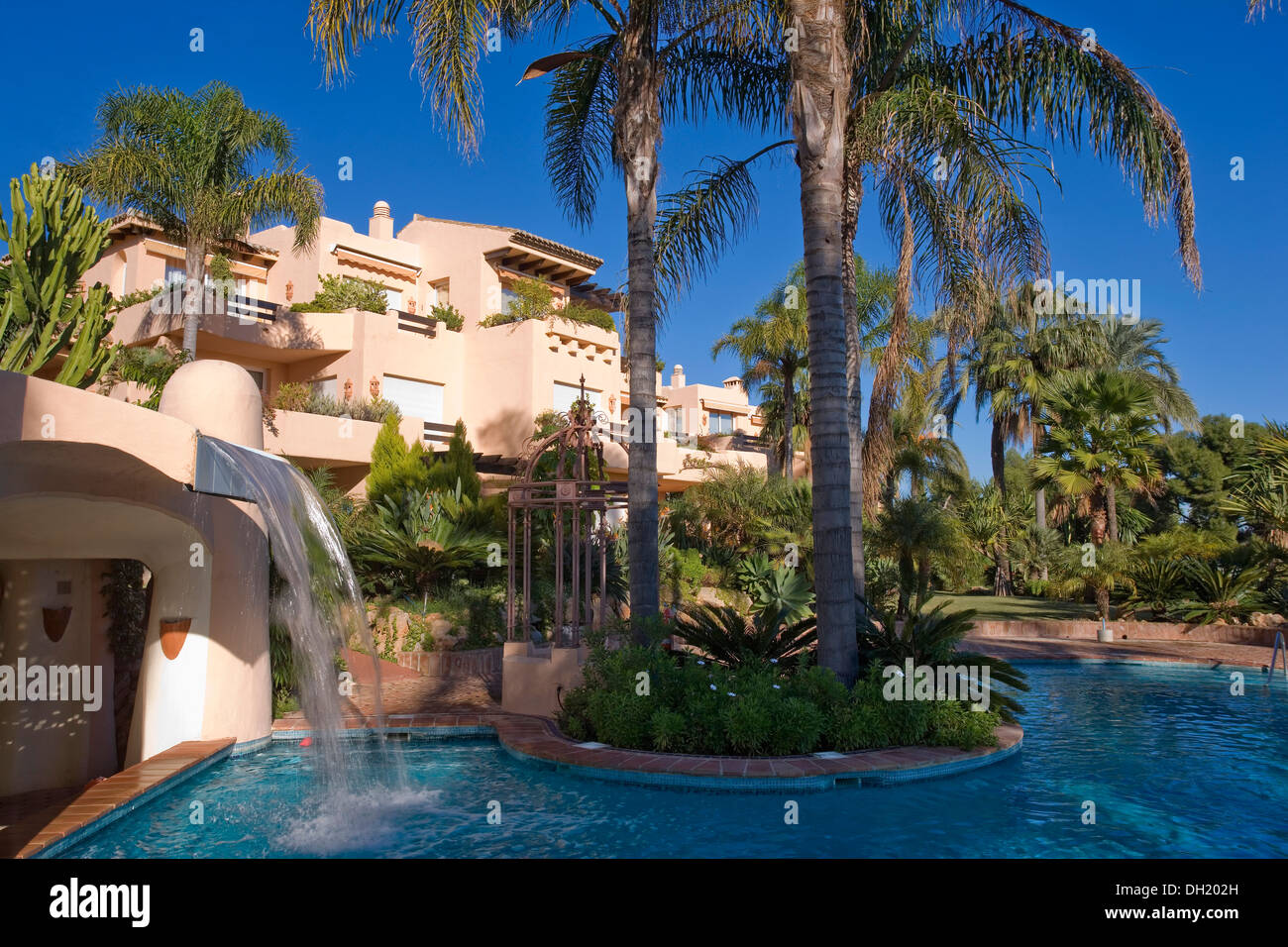 Palm trees beside swimming pool with small water chute in garden of stock photo royalty free for Best palm tree for swimming pool