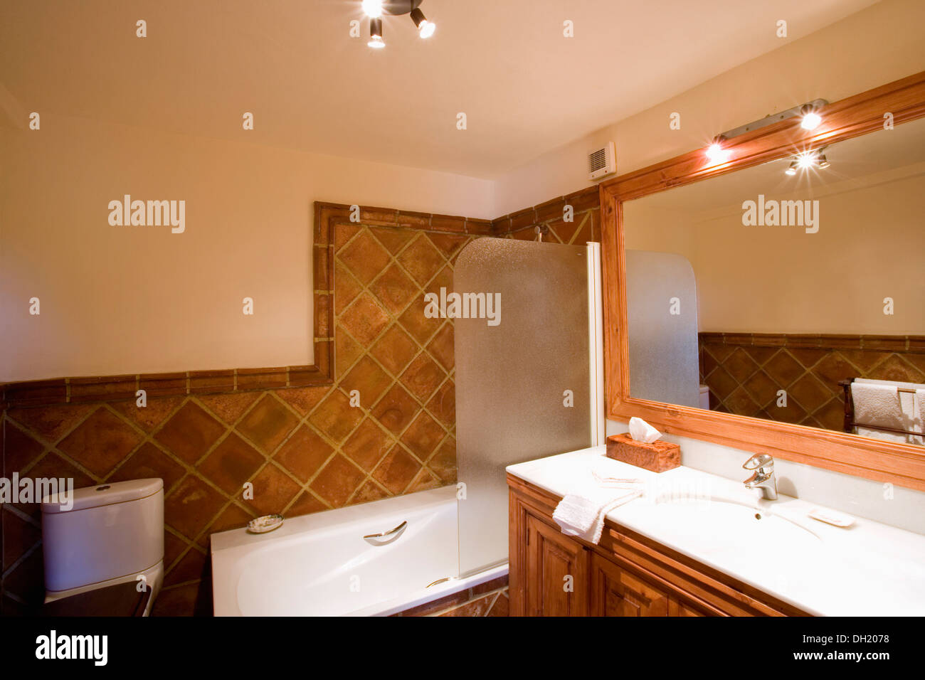 Glass screen on bath in modern bathroom with terracotta wall tiles glass screen on bath in modern bathroom with terracotta wall tiles and lighted mirror above basin in vanity unit dailygadgetfo Gallery
