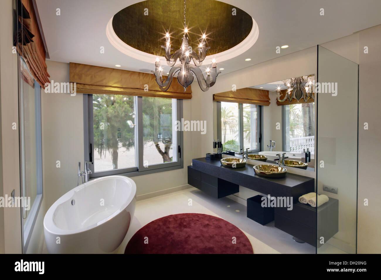 Oval freestanding bath and circular rug in modern Spanish bathroom ...
