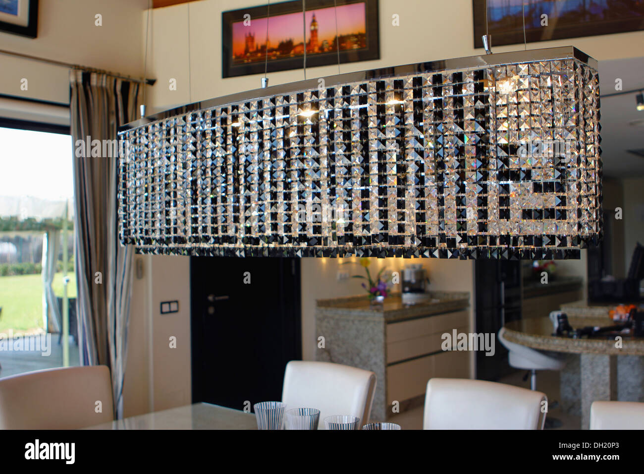 Large rectangular glass light fitting above table in modern dining ...