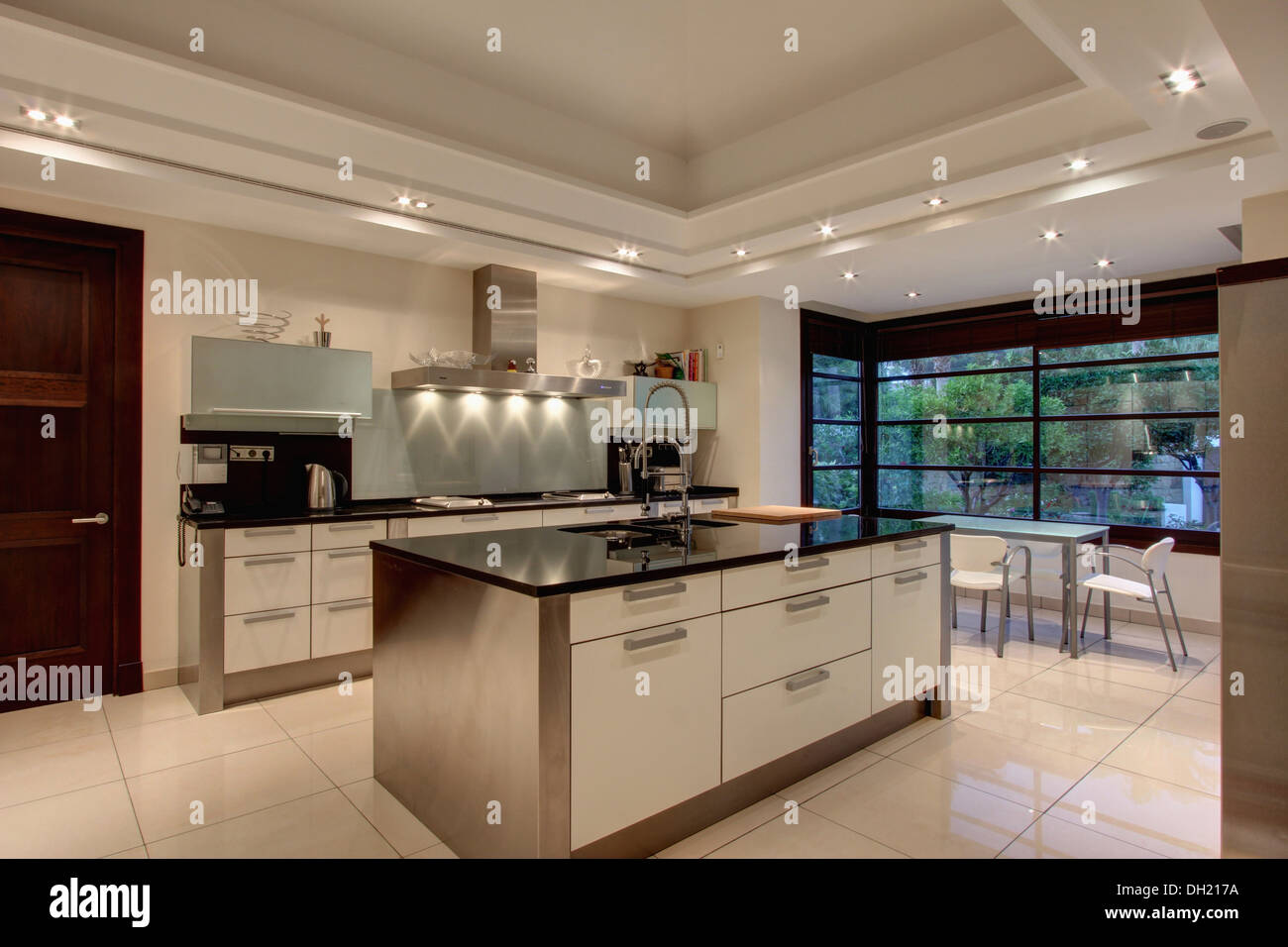 Down lighting on false ceiling in modern Spanish kitchen with stainless  steel island unit and white ceramic tiled floor