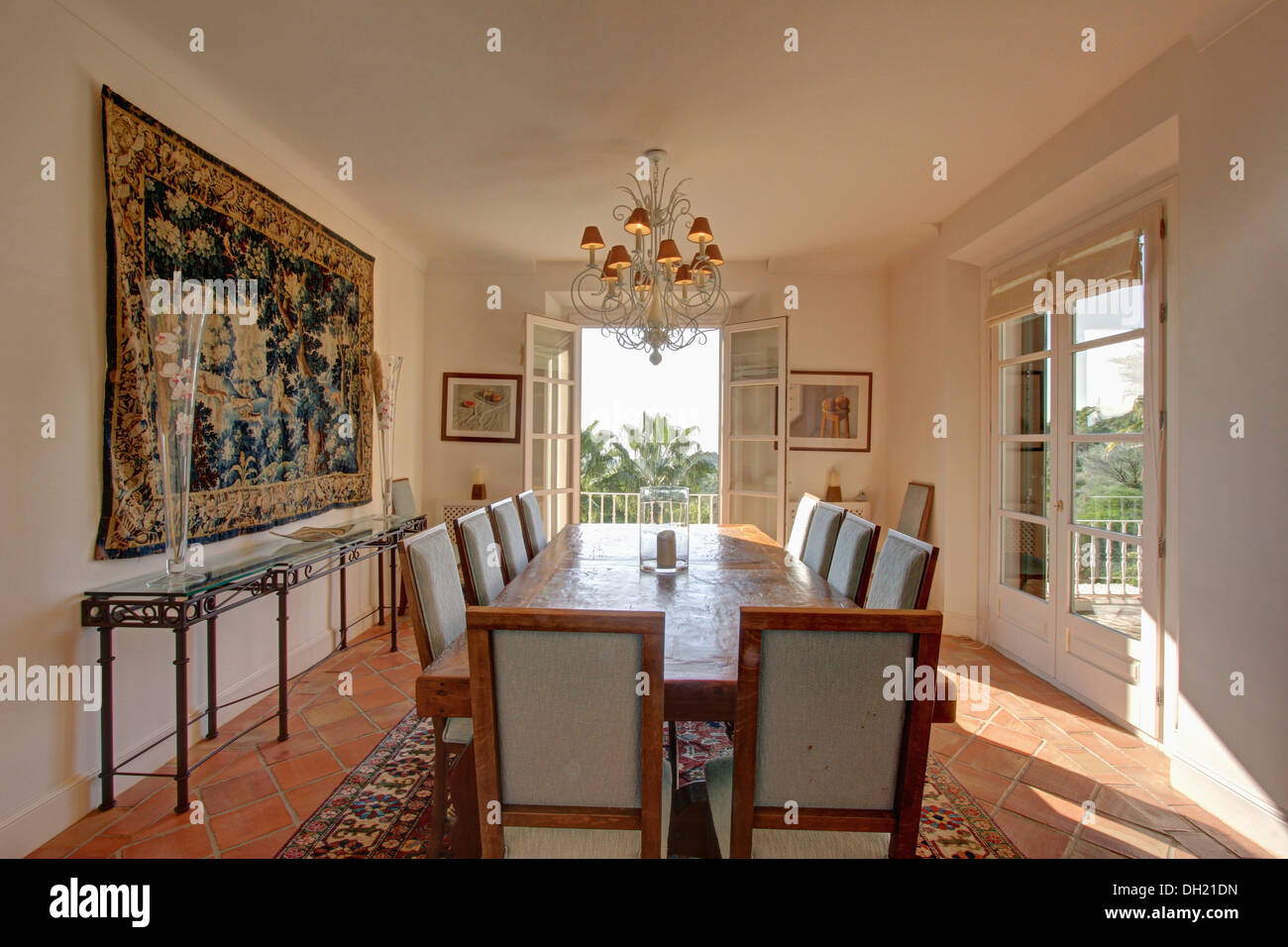 Large tapestry on wall above glassmetal console table in sunny large tapestry on wall above glassmetal console table in sunny white dining room with pale wood table and upholstered chairs geotapseo Images