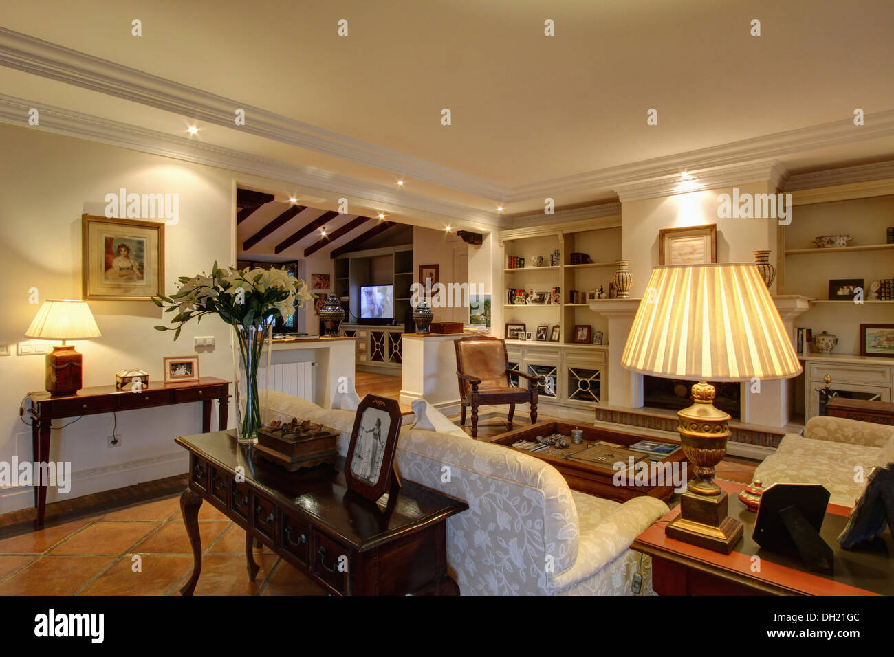 Lighted Lamps And Down Lighting In Comfortable Spanish Living Room With Console Table Behind Sofa