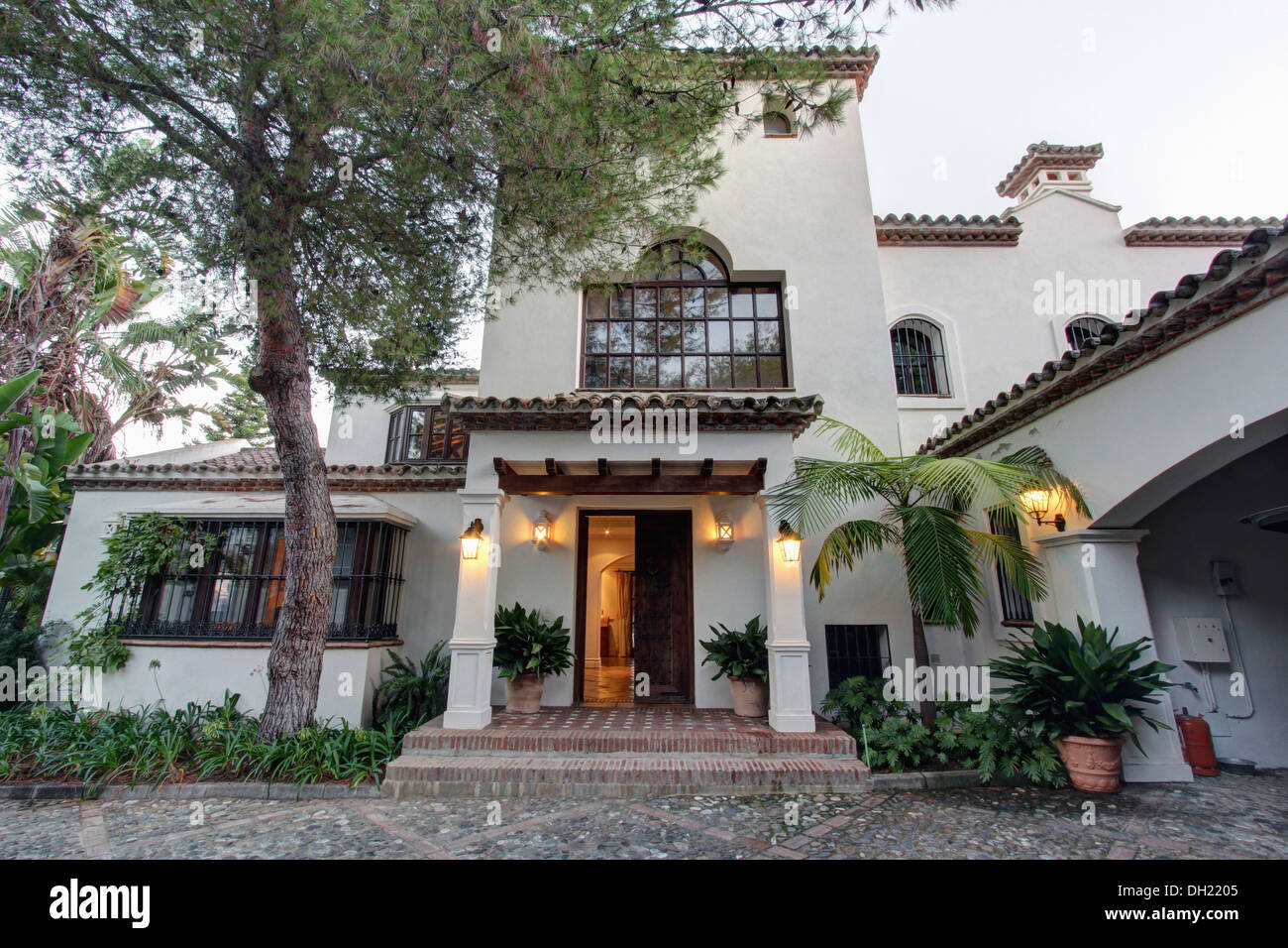 Tall Tree Beside Large Traditional Spanish Villa With Wall Lights On Porch Below Arched Window