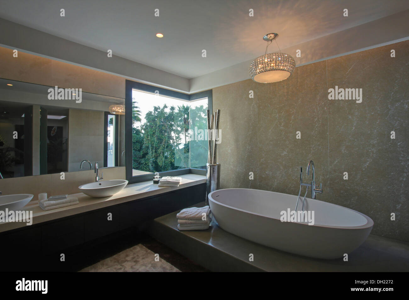 Glass light above raised oval bath in modern marble Spanish ...