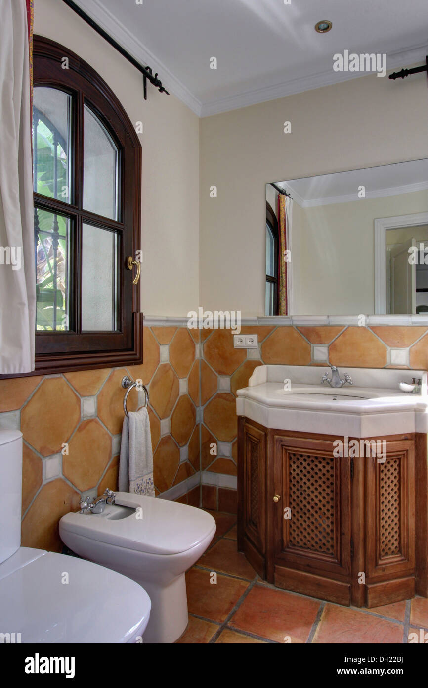 terracotta wall tiles to dado height in spanish bathroom with wooden fretwork doors on vanity unit with white basin - Bathroom Tiles Height