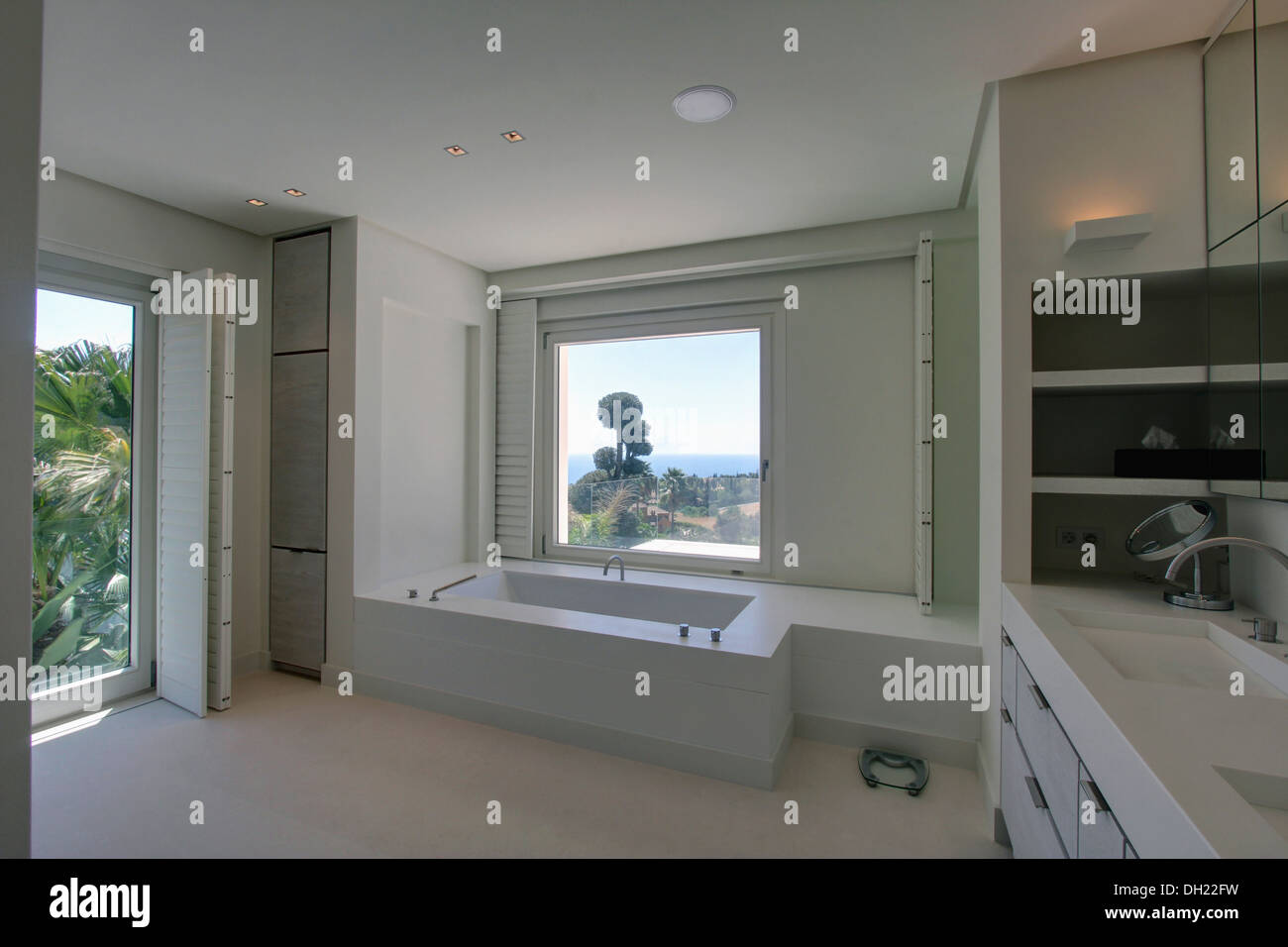 Window above bath in white Spanish bathroom with white shutters on ...