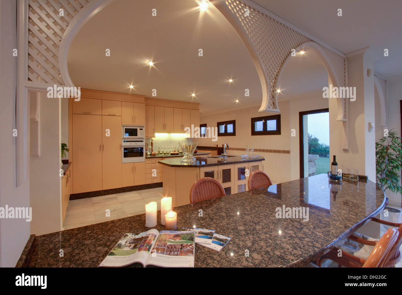 Granite topped breakfast bar in kitchen with decorative fretwork arch in newly built villa in southern spain