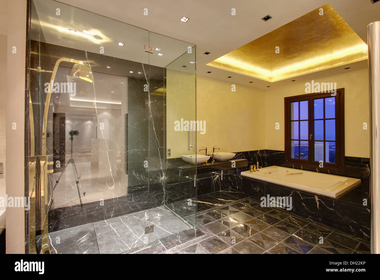 Glass screen on walk in shower in modern Spanish bathroom with ...