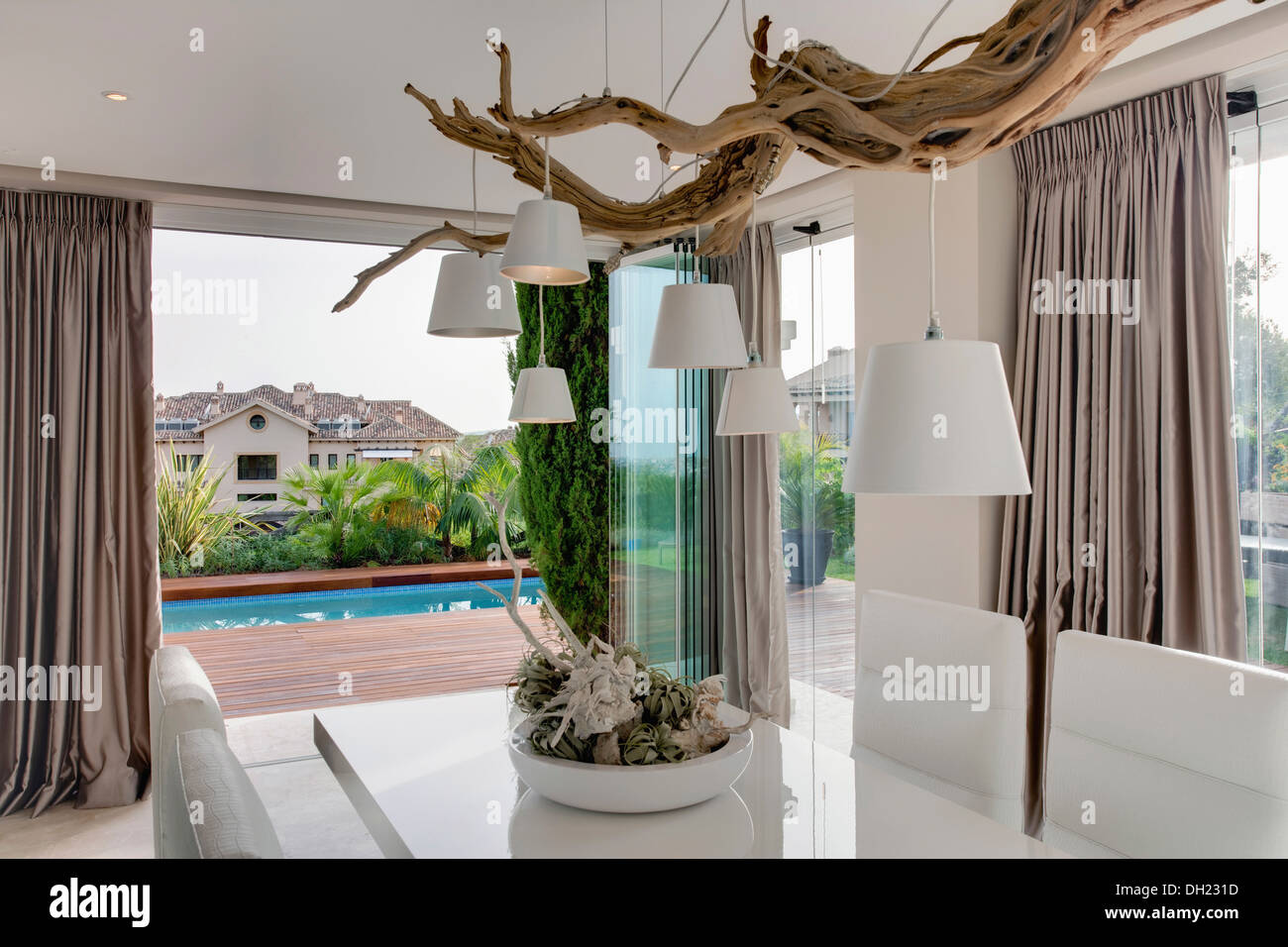 White Lampshades Hanging From Rustic Tree Branch Above Table In Modern Spanish Dining Room With Gray Silk Drapes On Glass Doors